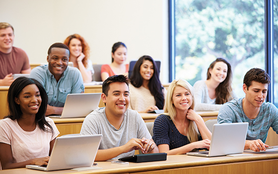 Image of students with laptops in a lecture classroom