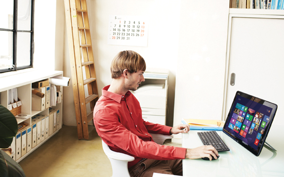 Image of man working on his computer from home office